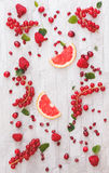 Fresh whole and sliced red fruits. Collection of fresh whole and sliced red fruits on white rustic background. Still life pattern background. Overhead view stock images