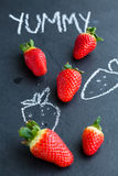 Yummy fresh whole strawberries. Fresh whole strawberries and chalk drawings and yummy word on dark background Stock Photography