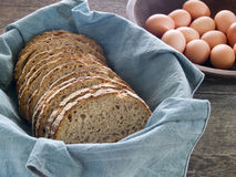 Fresh whole wheat bread and eggs. Fresh whole wheat bread in a basket with brown eggs in the background on a rustic wooden table Stock Photography