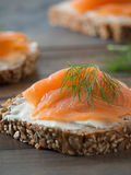 Fresh whole wheat sandwiches with smoked salmon. Close-up of some wheat sandwiches with smoked salmon on a wooden table Stock Images