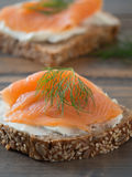 Fresh whole wheat sandwiches with smoked salmon. Close-up of some wheat sandwiches with smoked salmon on a wooden table Royalty Free Stock Photography
