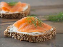 Fresh whole wheat sandwiches with smoked salmon. Close-up of some wheat sandwiches with smoked salmon on a wooden table Royalty Free Stock Photo