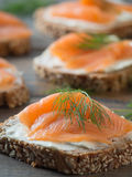 Fresh whole wheat sandwiches with smoked salmon. Close-up of some wheat sandwiches with smoked salmon on a wooden table Stock Photos