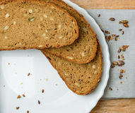 Fresh wholegrain bread sliced with plate on a wooden table Royalty Free Stock Images