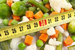 Fresh wholesome vegetables and measuring tape Stock Images