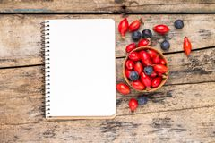 Fresh wild berries with paper notebook on wooden table. Royalty Free Stock Photo