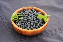 Fresh wild blueberries with green leaves in handmade wooden bowl Stock Images