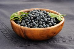 Fresh wild blueberries with green leaves in handmade wooden bowl Royalty Free Stock Photo