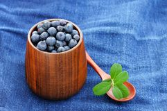 Fresh wild blueberries with green leaves in wooden vase and wood Stock Photos