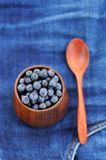 Fresh wild blueberries in wooden vase with wooden spoon on fraye Stock Photography