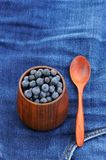 Fresh wild blueberries in wooden vase with wooden spoon on fraye Royalty Free Stock Photography