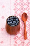 Fresh wild blueberries in wooden vase with wooden spoon on pink Royalty Free Stock Photos