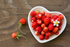Fresh wild strawberries in a Cup in the shape of a heart, symbol of love. Wooden background. The view from the top Royalty Free Stock Photos