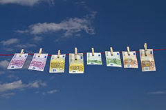 Fresh wind in the financial world. Bank notes fluttering on a clothesline against a blue sky in the wind royalty free stock images