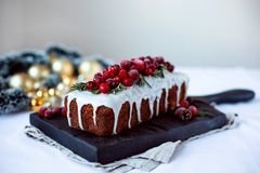 Fresh winter cake on wooden board decorated with cranberries, cones and golden balls stock photo