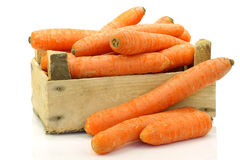 Fresh winter carrots in and around a wooden box Royalty Free Stock Photos