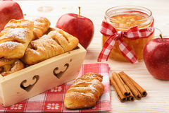 Fresh yeast buns with apple jam and cinnamon on white wooden background. Stock Photo