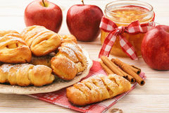 Fresh yeast buns with apple jam and cinnamon on white wooden background. Stock Photos