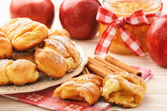 Fresh yeast buns with apple jam and cinnamon on white wooden background. Stock Photography