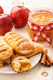 Fresh yeast buns with apple jam and cinnamon on white wooden background. Royalty Free Stock Photography