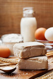 Fresh yeast and ingredients for baking on kitchen table. Product for preparing pizza or bread. Stock Images