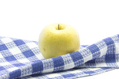 Fresh yellow apple healthy fruit on folded blue tablemat Royalty Free Stock Images