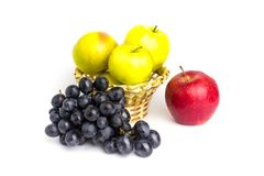 Yellow apples in a basket, red apple and a bunch of blue grapes on a white background royalty free stock image