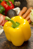 Fresh yellow bell pepper. Yellow bell pepper on cutting board in front of assortment of fresh salad ingredients stock photos