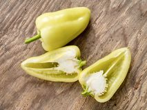 Fresh yellow bulgarian pepper whole and cut into a half. On wood. En background Royalty Free Stock Photography
