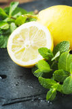 Fresh yellow lemon and green mint on the table Stock Photos