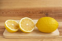 Fresh yellow lemon and half a lemon on a wooden table.  stock images