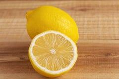 Fresh yellow lemon and half a lemon on a wooden table.  stock image