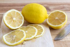 Fresh yellow lemon and slice of lemon with knife on a wooden table in the kitchen.  stock photo