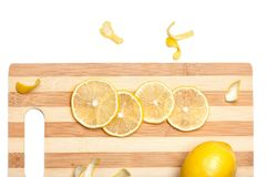 Fresh yellow lemon with slices on wooden bamboo kitchen board isolated. Closeup Royalty Free Stock Photos