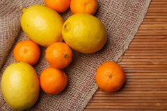 Fresh yellow lemons with orange mandarins on bag Stock Photo