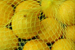 Fresh yellow lemons. In plastic netting In Market. Food background texture Royalty Free Stock Image