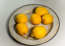 Fresh yellow lemons in vintage enamel plate. Close up royalty free stock photography