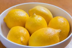 Fresh yellow lemons on a wooden background stock image