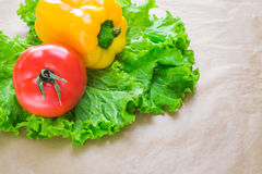 Fresh yellow paprika, tomatoes and green salad leaves on a grey background. Space for text. Healthy eating concept. Fresh yellow paprika, tomatoes and green Stock Photography