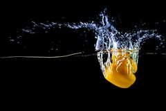 Fresh yellow paprika in water splashes on a black background. Yellow sweet pepper royalty free stock image