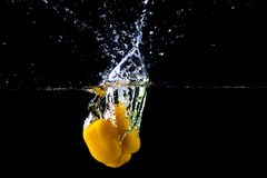 Fresh yellow paprika in water splashes on a black background. Yellow sweet pepper Royalty Free Stock Photos