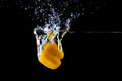 Fresh yellow paprika in water splashes on a black background. Yellow sweet pepper stock photography