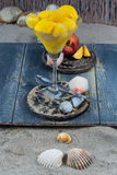 Fresh yellow peach ice-cream scoops in glass cone on the beach,. Fresh yellow peach ice-cream in glass cone on the beach on gray wooden background, summer Stock Photo
