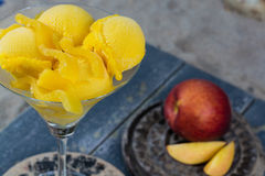 Fresh yellow peach ice-cream scoops in glass cone on the beach, Stock Photo