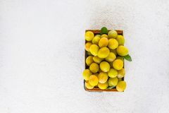 Yellow plums. Ripe fruits in a wooden box on white background. Fresh yellow plums. Ripe fruits in a wooden box on white background stock photography