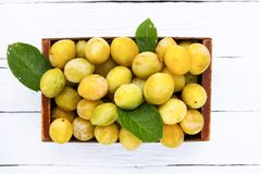 Fresh yellow plums. Ripe fruits in a box on white boards background stock photos