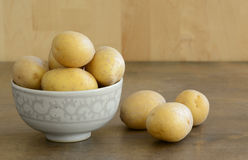 Fresh yellow potatoes in the small bowl and some o. N dark wooden table stock photography