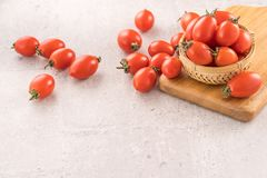 Fresh yellow and red cherry tomatoes in a basket on a cement board, close up, copy space, top view. Fresh yellow and red cherry tomato in a basket on a cement stock photography