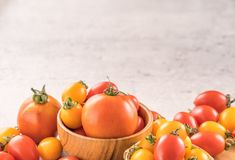 Fresh yellow and red cherry tomatoes in a basket on a cement board, close up, copy space, top view royalty free stock photography