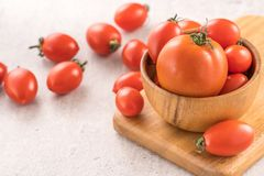 Fresh yellow and red cherry tomatoes in a basket on a cement board, close up, copy space, top view royalty free stock images